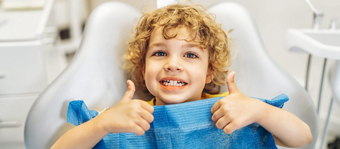 happy-cute-little-boy-in-dental-ofiice-showing-thumbs-up-after-treatment (1)-min